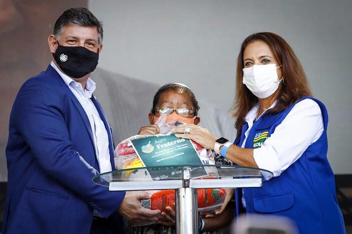 Diretor-geral do Senar, Daniel Carrara, e a primeira-dama de Goiás, Gracinha Caiado, entregam a cesta à Antônia Batista de Jesus.